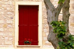 Dark red shutters in the wall of a house in France. by Tom Haseltine