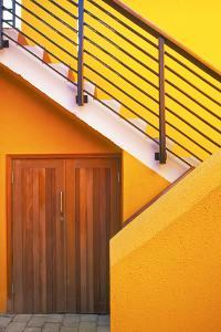 Geometric view of a yellow and orange stairway. by Tom Haseltine