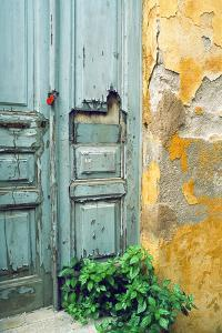 Red lock on a weathered blue door. by Tom Haseltine