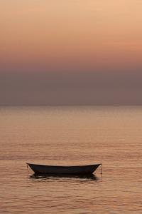 Rowboat at anchor in the water at sunset. by Tom Haseltine