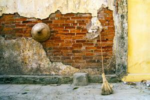 Still-life of a hat and broom against a weathered wall in Vietnam. by Tom Haseltine