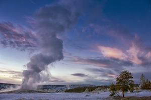 Eruption of Old Faithful Geyser after Sunset. Yellowstone National Park, Wyoming. by Tom Norring