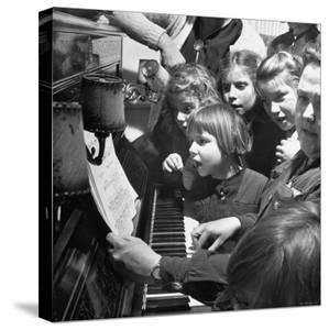 Children Singing Around the Piano at Orphanage by Tony Linck