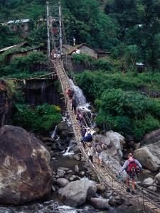 People Crossing Sagging Suspension Bridge Over Khudi Khola on Annapurna Circuit, Nepal by Tony Wheeler