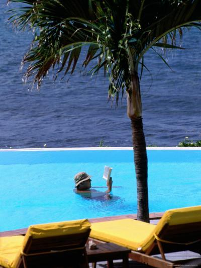 Tourist Reading Book in Swimming Pool with Ocean in Background, Palm Tree in Foreground-Pascale Beroujon-Photographic Print