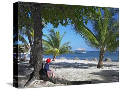 Tourist resting under palm trees on beach at Palmetto Bay, Roatan Island, Honduras-Tim Fitzharris-Stretched Canvas Print