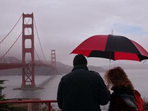 Tourists Use an Umbrella During a Light Rain, Looking at the Golden Gate Bridge in San Francisco