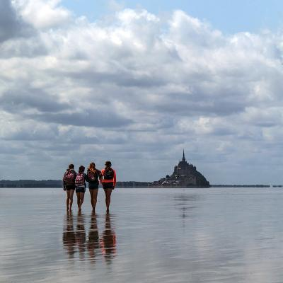 Tourists Walk the Sea Floor at Low Tide to the World Heritage Site Mont Saint Michel Monastery-Babak Tafreshi-Photographic Print