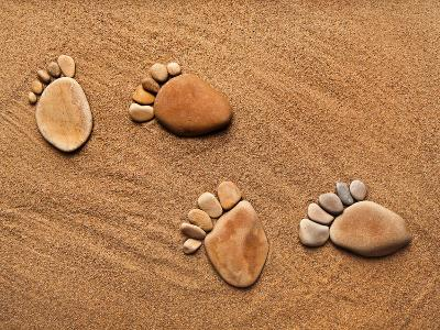 Trace Feet Steps Made Of A Pebble Stone On The Sea Sand Backdrop-Madlen-Photographic Print