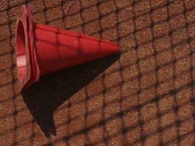 Traffic Cone Lying in the Shadow of a Net--Photographic Print