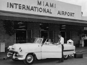 Travelers in a Chevy Bel Air Convertible at the Miami International Airport, 1954 August 22