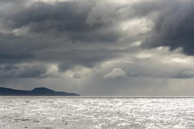 Australia, Tasmania, Tasman Sea. Dramatic line of sun on horizon through storm clouds and rain