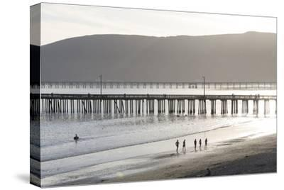 USA, California, Avila Beach. Silhouetted Beach Walkers Approach Pier End of Day