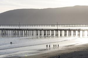 USA, California, Avila Beach. Silhouetted Beach Walkers Approach Pier End of Day by Trish Drury