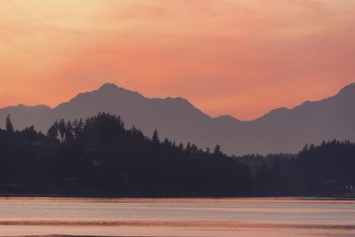 USA, Washington State. Olympic Mountains silhouetted in dramatic light. Calm Puget Sound.