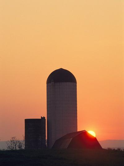 Twilight View of a Barn and Silo Silhouetted against the Sun-Kenneth Garrett-Photographic Print