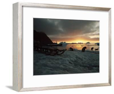 Twilight View of Sled Dogs and Sled on Shore with Boat in Distance-Bill Curtsinger-Framed Photographic Print