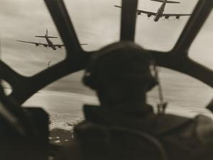 Two B-29 Super-Fortresses Drop Bombs over Malaya as Seen from the Cockpit of Third Bomber, 1943-45