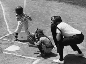 Two Boys Playing Baseball; Adult Umpire Standing Behind Home Plate