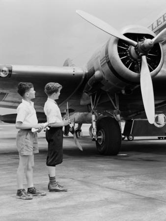https://imgc.artprintimages.com/img/print/two-boys-standing-next-to-propeller-aeroplane-holding-toy-plane_u-l-q10brkx0.jpg?p=0