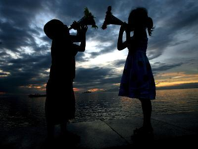 Two Children Sound their Toy Trumpets Along the Manila Baywalk in Manila, Philippines-Mike F. Alquinto-Photographic Print