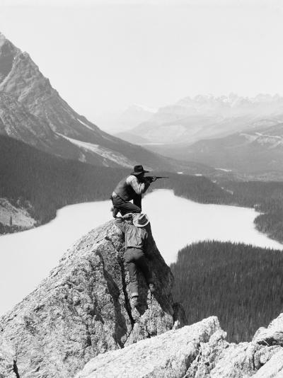 Two Cowboys on Top of Rocky Crag, One Man Kneeling, Aiming Hunting Rifle-H^ Armstrong Roberts-Photographic Print