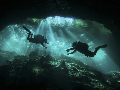 Two Divers Silhouetted in Light at Entrance to Chac Mool Cenote, Mexico--Photographic Print