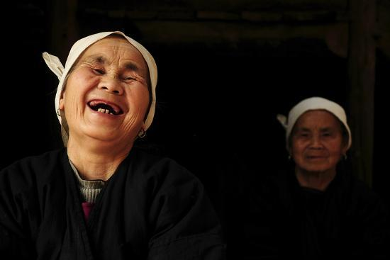Two Dong Women, One Laughing, in a Dark Room, Sanjiang Dong Village, Guangxi, China-Enrique Lopez-Tapia-Photographic Print