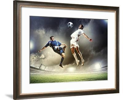 Two Football Players in Jump to Strike the Ball at the Stadium-Sergey Nivens-Framed Photographic Print