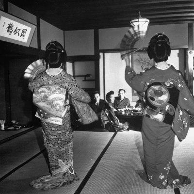 https://imgc.artprintimages.com/img/print/two-geishas-dancing-with-fans-on-stage-as-guests-and-other-geshias-watch-from-dinner-table_u-l-p766vh0.jpg?p=0
