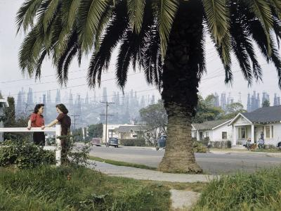 Two Girls Chat on a Street with Oil Derricks in the Background-B^ Anthony Stewart-Photographic Print