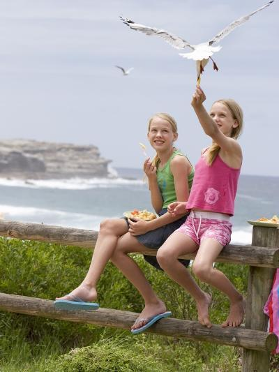 Two Girls Feeding Chips to a Seagull at the Beach-Louise Hammond-Photographic Print