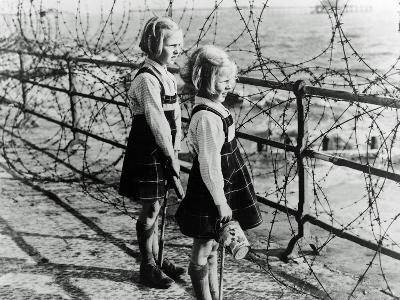 Two Girls on the South Coast of England Look Out Toward the Beach Through a Barbed Wire Fence--Photographic Print