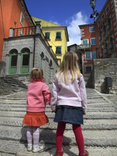 Two Girls on Ulica 1 Maja Street with Colourful Buildings-Ruth Eastham & Max Paoli-Photographic Print