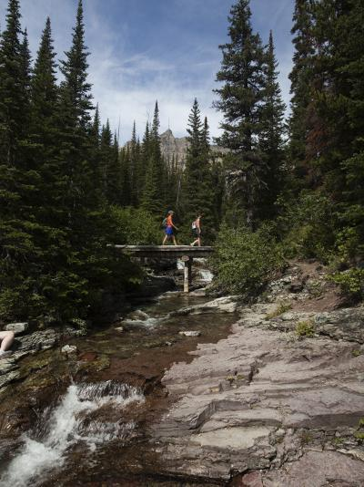 Two Hikers Cross a Small Stream in the Montana Backcountry-Michael Hanson-Photographic Print