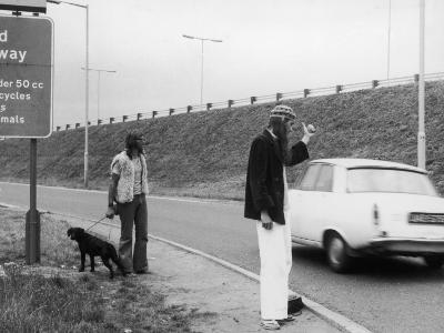 Two Hippy Hitch-Hikers, Thumbing a Lift, But Will Anyone Stop for Them?--Photographic Print