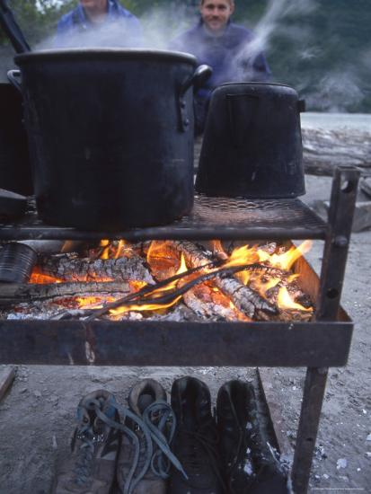 Two Men at Camp Are Drying their Shoes under Camp Cook Fire-Kate Thompson-Photographic Print