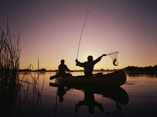Two Men Catching Fish In Canoe At Sunset Photographic Print By
