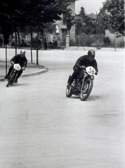 Two Motorcyclists Racing Along a Road, Otorcycles are Numbered 46 and 36-A^ Villani-Photographic Print