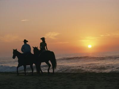 Two People on Horseback Ride Along an Ocean Shoreline at Sunset-Roy Toft-Photographic Print