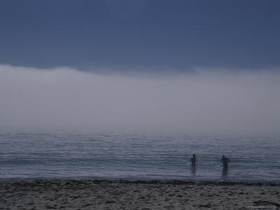 Two People Test the Frigid Water as a Weather Front Rolls Through-Stacy Gold-Photographic Print
