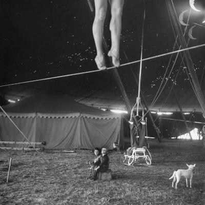 Two Small Children Watching Circus Performer Practicing on Tightrope, Her Legs Only Visible-Nina Leen-Photographic Print