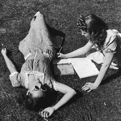 Two Teenage Girls (14-16) on Grass, One Doing Homework