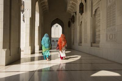 Two Traditionally Dressed Women Walk in a Corridor of the Sultan Qaboos Grand Mosque-Michael Melford-Photographic Print