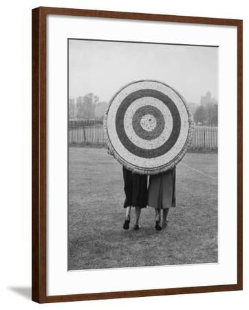 Two Women Holding Up Archery Target in Field--Framed Photographic Print