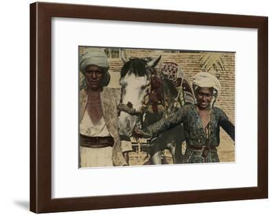 Two Women Stand at Either Side of the Decorated Horses They Groom-Eric Keast Burke-Framed Photographic Print