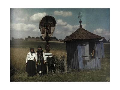 Two Women Stand Beside a Roadside Shrine-Hans Hildenbrand-Photographic Print