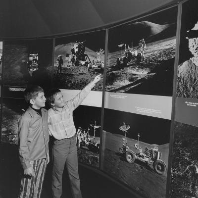 Two Young Boys Looking at Images of a Moon Landing--Photographic Print