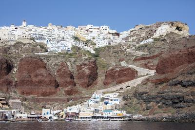 Typical Greek Village Perched on Volcanic Rock with White and Blue Houses and Windmills, Santorini-Roberto Moiola-Photographic Print