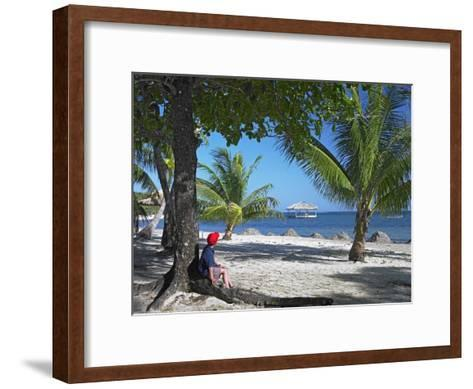 Tourist resting under palm trees on beach at Palmetto Bay, Roatan Island, Honduras-Tim Fitzharris-Framed Art Print